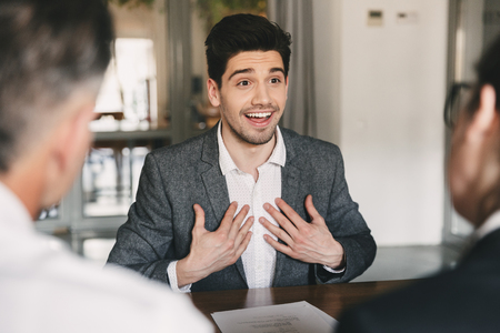 Business, career and placement concept - satisfied caucasian man 30s rejoicing and expressing surprise when hiring during job interview with employees in office