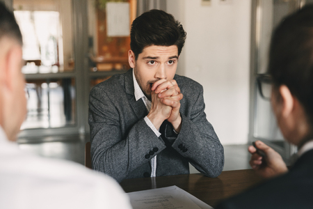 Business, career and placement concept - caucasian uptight male applicant worrying and putting fists together during job interview in office with board of directors Stock Photo