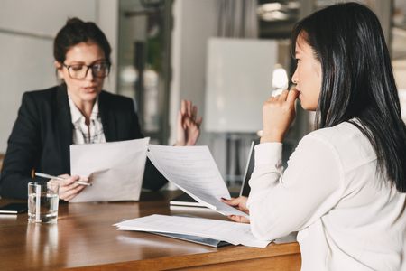 Image of nervous asian woman looking and talking to businesswoman while sitting at table in office during job interview - business, career and recruitment concept Stock Photo