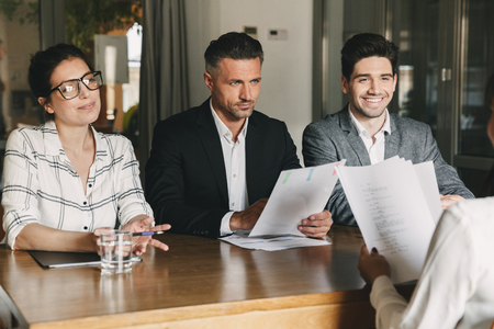 Business, career and placement concept - three executive directors or head managers sitting at table in office and interviewing woman during meeting Stock Photo