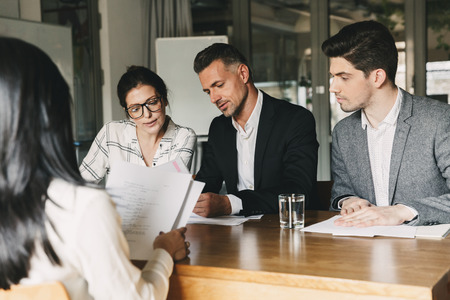 Business, career and recruitment concept - team of employers in formal wear sitting at table in office and interviewing woman for job in big corporation