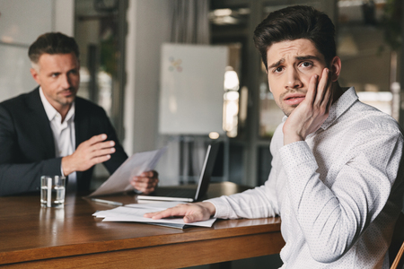 Business, career and placement concept - stressed nervous man worrying during job interview in office while negotiating with caucasian businessman or director