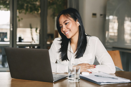 Photo of adorable asian female worker 20s wearing white shirt and earbud smiling while sitting at table in office and working on laptop Stock Photo