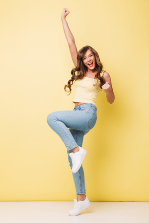 Full length photo of pleased woman 20s with long brown hair rejoicing and screaming in delight with clenching fists isolated over yellow background Archivio Fotografico