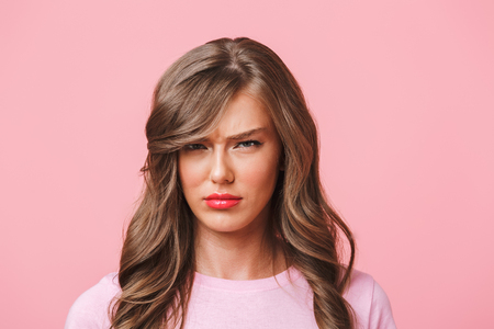 Photo closeup of upset woman with long curly hair in basic t-shirt pouting and frowning in resentment isolated over pink background