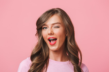 Image closeup of young attractive woman 20s with long curly hairstyle and seductive look winking at camera with smile isolated over pink background Stockfoto - 104563500