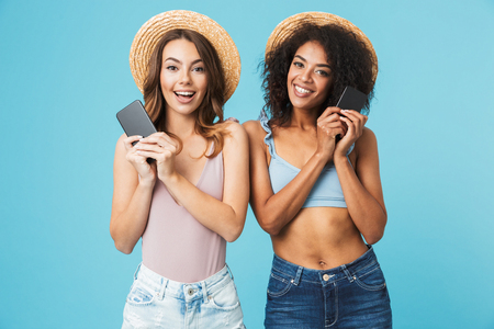 Two lovely multiethnic women 20s wearing straw hats smiling and both holding smartphone while looking at camera isolated over blue background Stock Photo