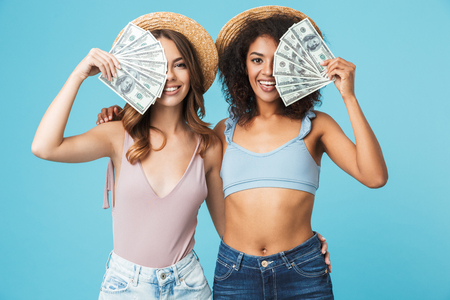 Photo of caucasian and african american women wearing straw hats and summer clothing covering their faces with dollar banknotes isolated over blue background
