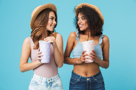 Two beautiful young women 20s with different type of skin wearing straw hats looking at each other while holding paper cups with soda or cold drinks isolated over blue background