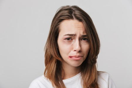 Wizerunek smutnej, niepełnosprawnej dziewczyny z zadrapaniami i siniakami na twarzy.