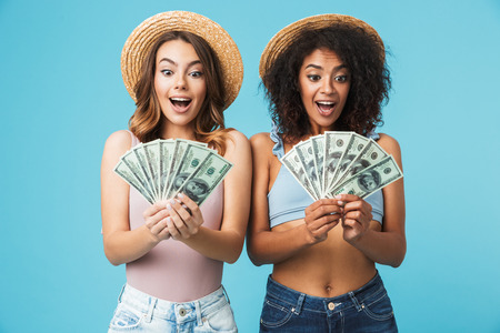 Portrait of two excited women with different type of skin wearing straw hats and summer clothing looking at lots of money holding in hands isolated over blue background