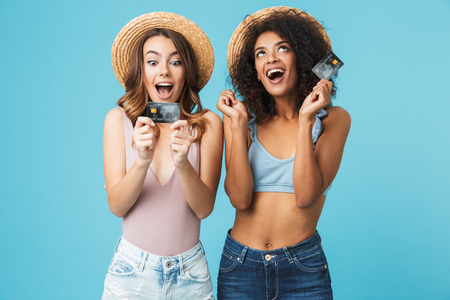Photo of two joyful multiethnic women 20s wearing straw hats and summer clothing screaming while holding credit cards isolated over blue background