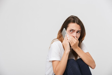 Abused scared woman with wounds on her face calling with mobile phone isolated over white background