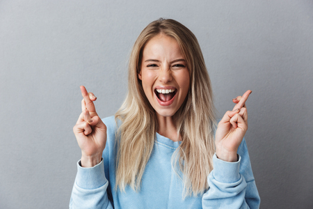 Portrait of a cheerful young girl in blue sweatshirt holding fingers crossed for good luck isolated over gray background