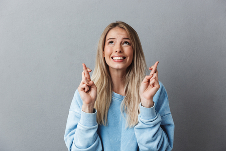 Portrait of a joyful young girl in blue sweatshirt holding fingers crossed for good luck isolated over gray background