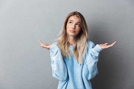 Portrait of a confused young blonde girl shrugging shoulders isolated over gray background Stockfoto