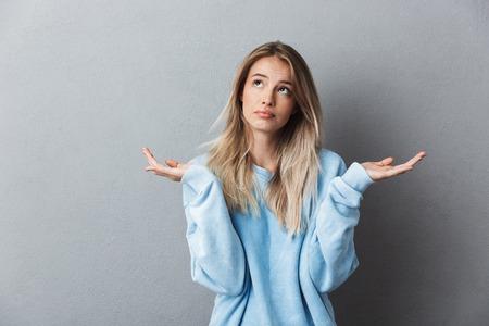 Portrait d'une jeune fille blonde confuse en haussant les épaules isolé sur fond gris Banque d'images