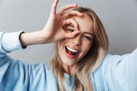 Close up of smiling young blonde girl taking a selfie and showing ok gesture isolated over gray background