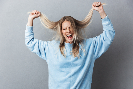 Portrait of a stressed young blonde girl examining her hair and screaming isolated over gray background