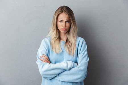 Portrait of an upset young girl in blue sweatshirt standing with arms folded isolated over gray background Stock Photo