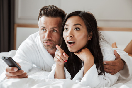 Multiethnic couple handsome man and excited woman wearing white bathrobe lying in home bedroom or hotel apartment with remote control while watching television