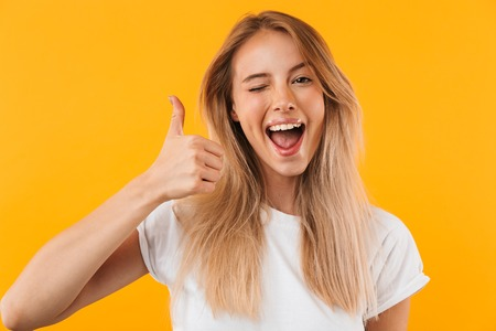 Portrait of a cheerful young blonde girl showing thumbs up and winking isolated over yellow background