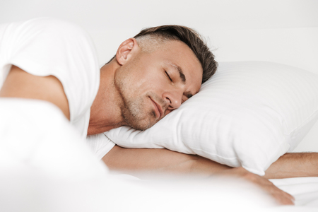 Handsome man sleeping in bed at home Stock Photo