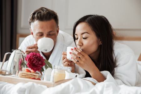 Attractive young couple dressed in bathrobes having romantic breakfast while lying on bed and drinking coffee