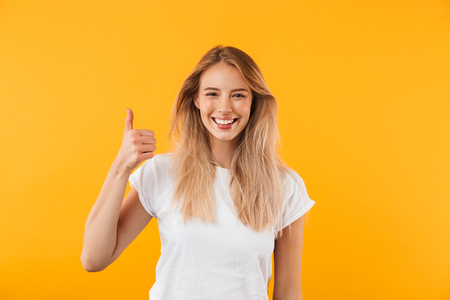 Portrait of a cheerful young blonde girl showing thumbs up isolated over yellow background