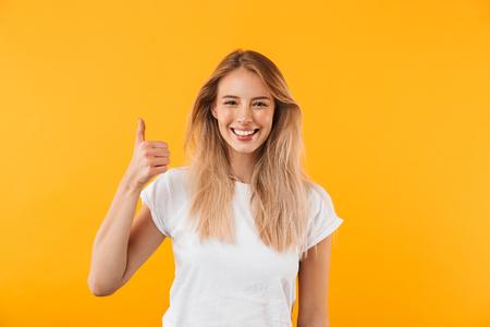 Portret van een vrolijk jong blondemeisje die duimen tonen die omhoog over gele achtergrond worden geïsoleerd