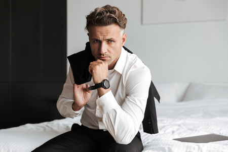 Exhausted man dressed in suit sitting on bed and looking at camera Stock Photo