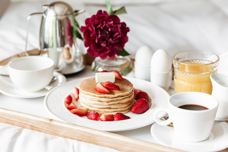 Breakfast in bed with white linen. Pancakes, boiled eggs, coffee, orange juice on tray at hotel room Stockfoto