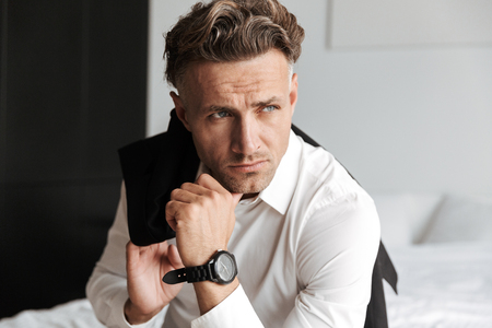 Concentrated man dressed in suit sitting on bed and looking away Stock Photo