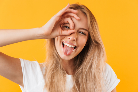 Close up portrait of a smiling young blonde girl showing ok gesture and sticking her tongue out isolated over yellow background Stock Photo