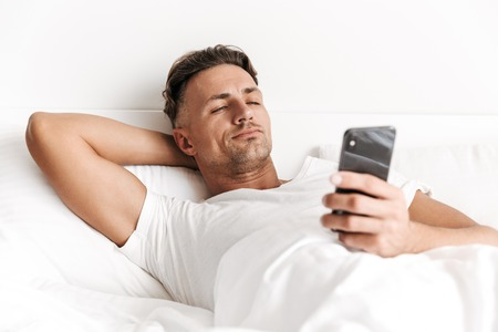 Handsome man using mobile phone while laying in bed