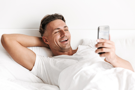 Laughing man using mobile phone while laying in bed Banco de Imagens