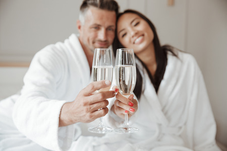 Blurry image closeup of happy loving couple in white bathrobes holding and clinking glasses with champagne while hugging at hotel room 写真素材