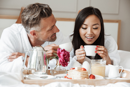 Happy young couple dressed in bathrobes having romantic breakfast while lying on bed and drinking coffee