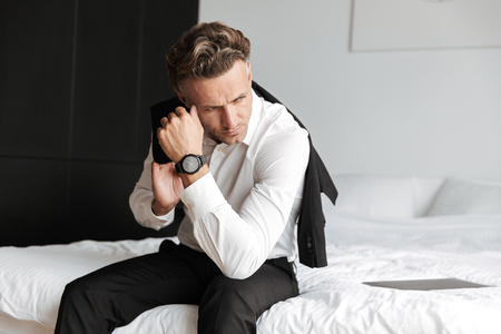 Depressed man dressed in suit sitting on bed and looking away