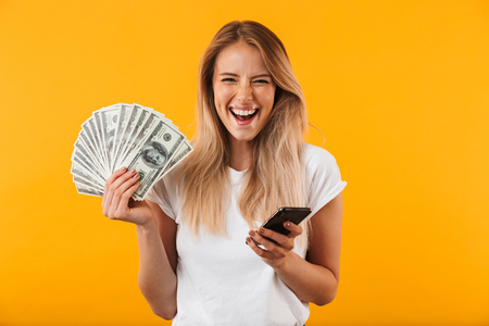 Portrait of an excited young blonde girl showing bunch of money banknotes and holding mobile phone isolated over yellow background