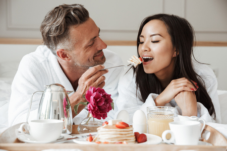 Smiling young couple dressed in bathrobes having romantic breakfast while lying on bed, man feeding woman