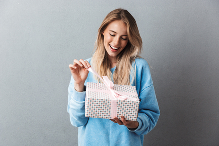 Portrait of an excited young blonde girl unwrapping present box isolated over gray background
