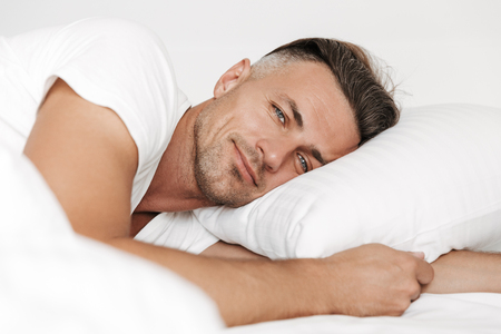 Smiling man lying in bed and looking at camera