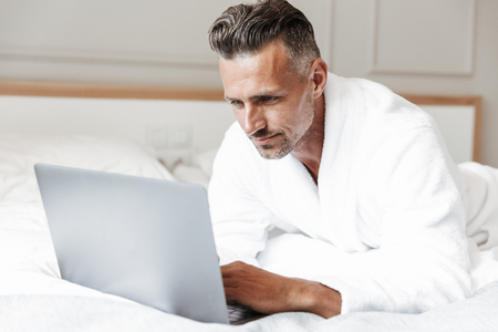 Portrait of masculine adult man with gray beard wearing white housecoat looking at silver laptop while lying on bed in room or hotel apartment