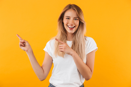 Portrait of a joyful young blonde girl pointing at copy space isolated over yellow background