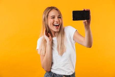 Cheerful young blonde girl taking a selfie with mobile phone isolated over yellow background Stock Photo