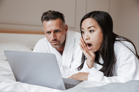 Surprised young couple dressed in bathrobes lying on bed with laptop computer