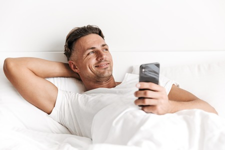 Smiling man holding mobile phone while laying in bed Banco de Imagens