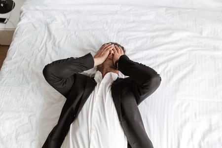 Hombre cansado vestido con traje acostado en la cama con los brazos en el rostro Foto de archivo