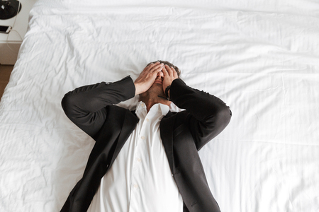 Tired man dressed in suit lying on bed with arms on his face